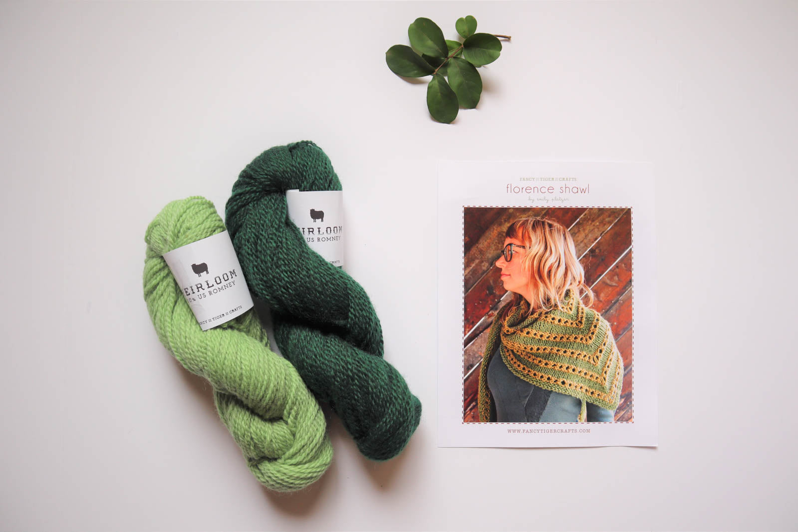 Lay flat photo of two skeins of yarn in light green and spruce, knitting pattern and green foliage.