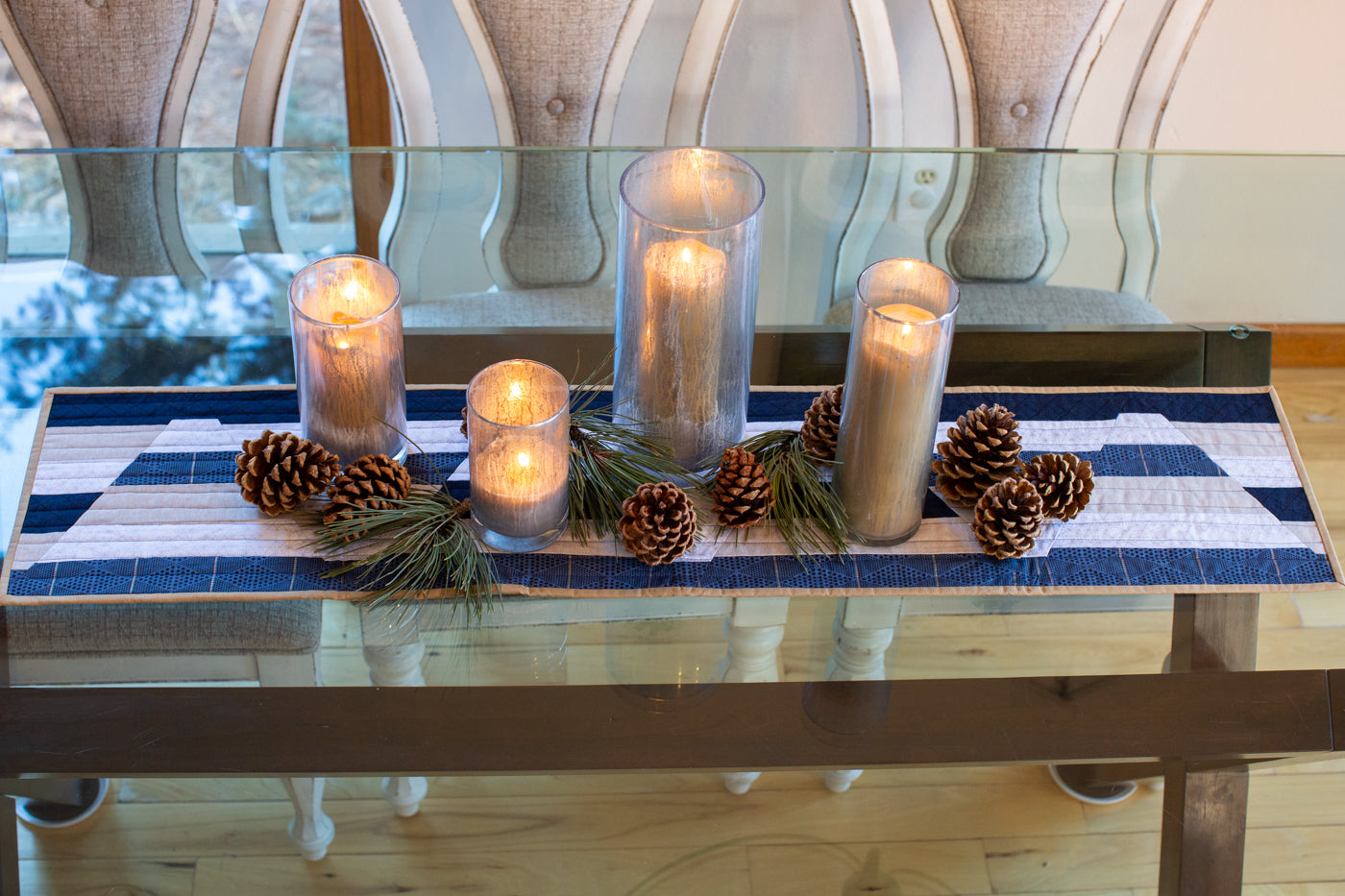 Photograph taken from above the glass kitchen table to showcase the table runner.  On top of the table runner sits lit candles, in tall candle holders, with pinecones and pine needle bunches intertwined.
