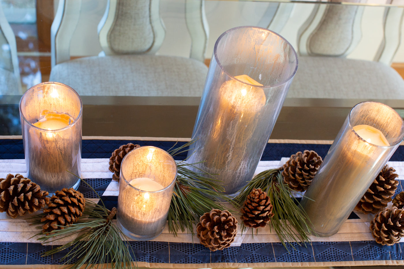 Photograph taken looking down at the kitchen table with a table runner.  The table runner is navy blue, white, tan and a deep blue.  There are candles lit in tall glass candle holders with pinecones and pine needle bunches at the base of the candles to create a holiday atmosphere.