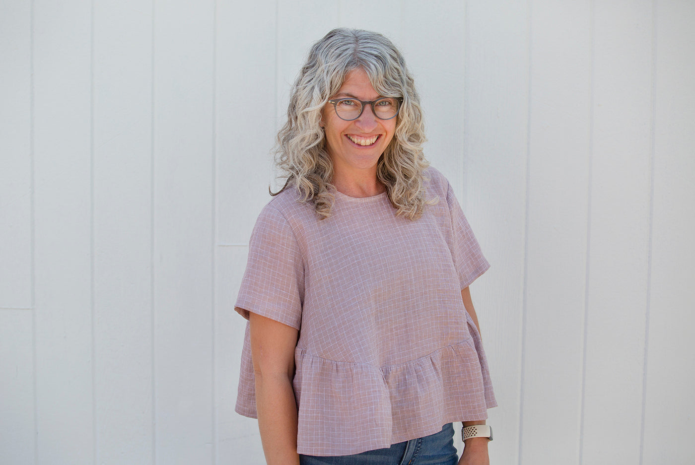 This is a photo of a woman wearing a pink ruffled shirt standing against a white wall.
