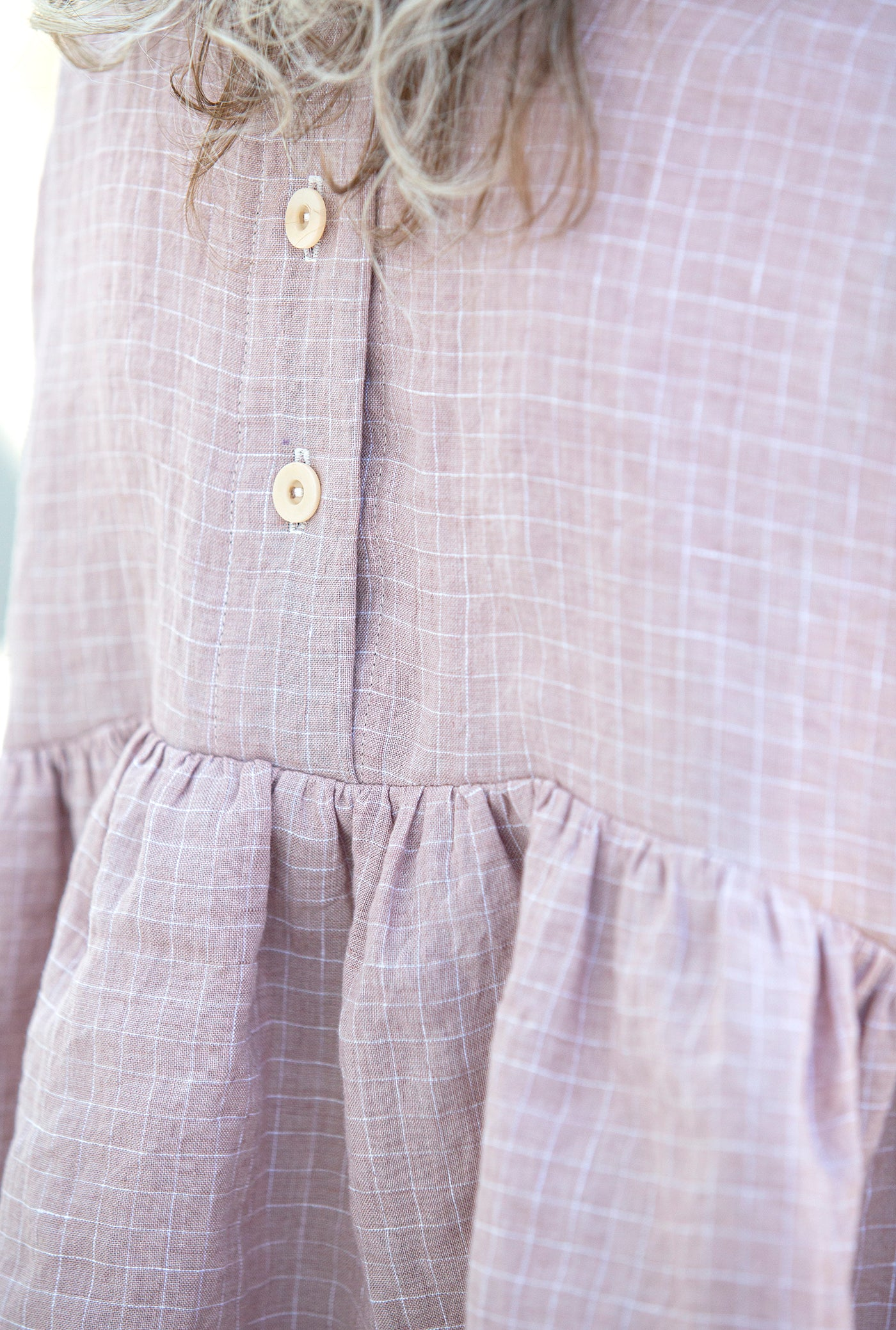 This is an up close photo of a pink shirt's ruffles and button closures