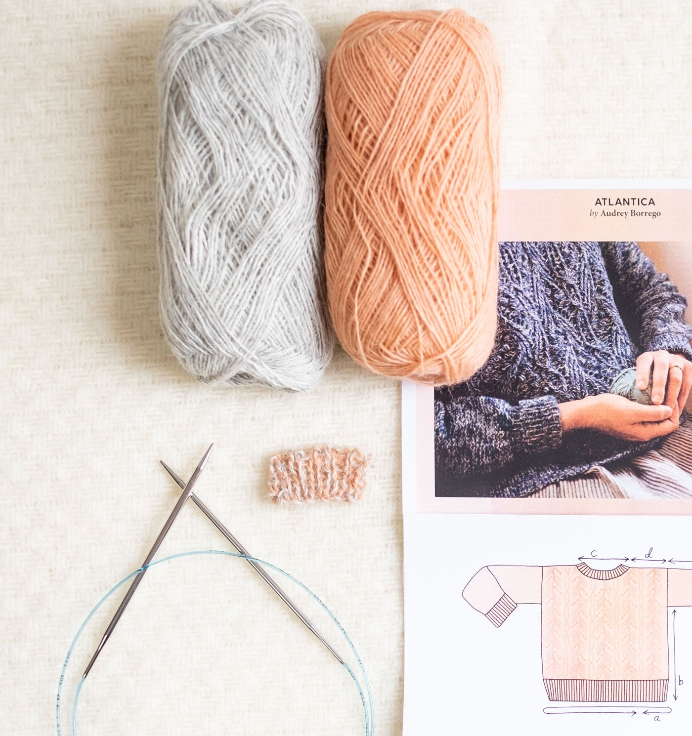 A ball of Light Ash Heather and a ball of Peach Einband yarn lay atop a printed page of the Atlantica Pullover pattern. A pair of stainless steel circular knitting needles and a small swatch of the two hues marled together lay next to the pattern page.