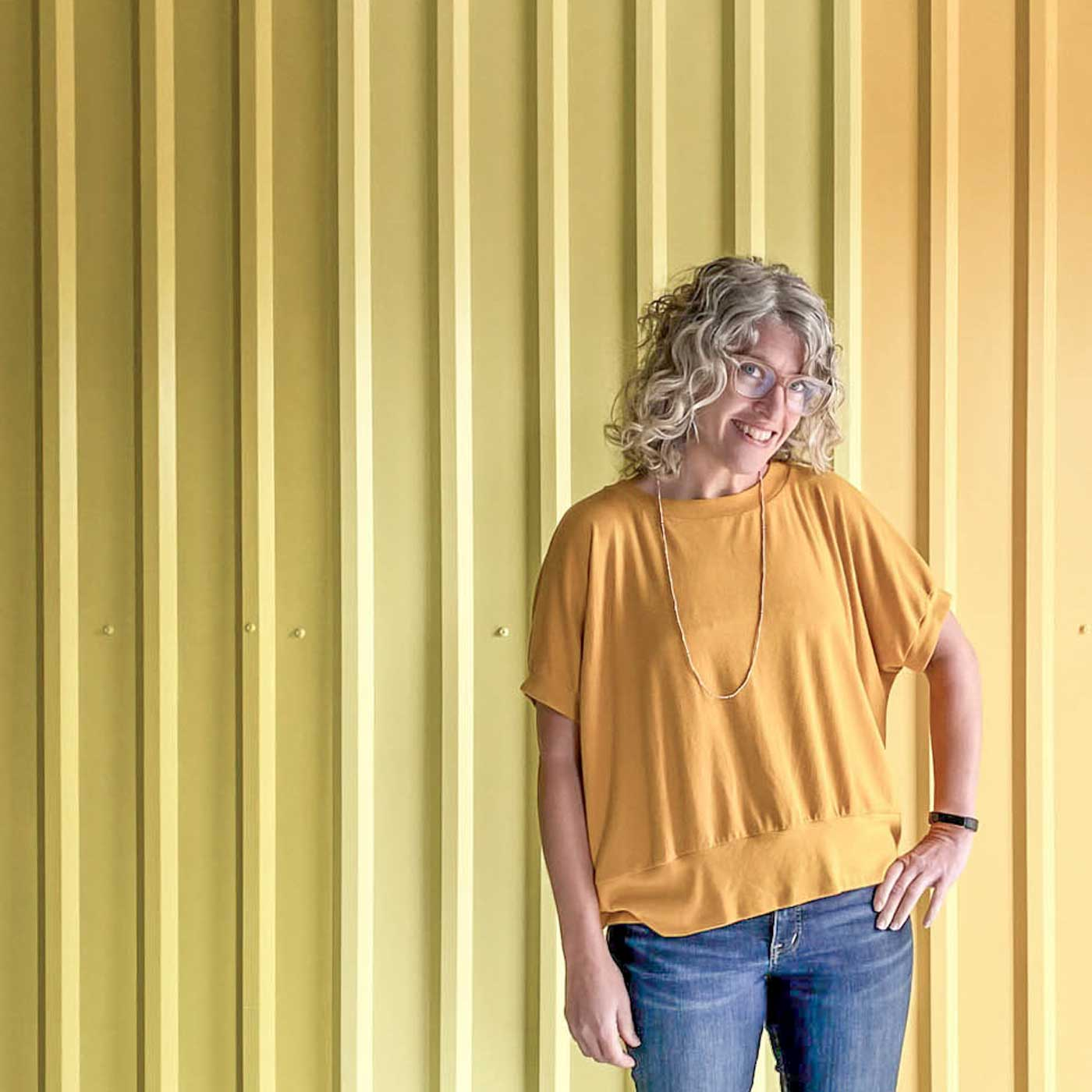 Jaime wearing a golden yellow Hosta tee standing in front of yellow ombre wall.