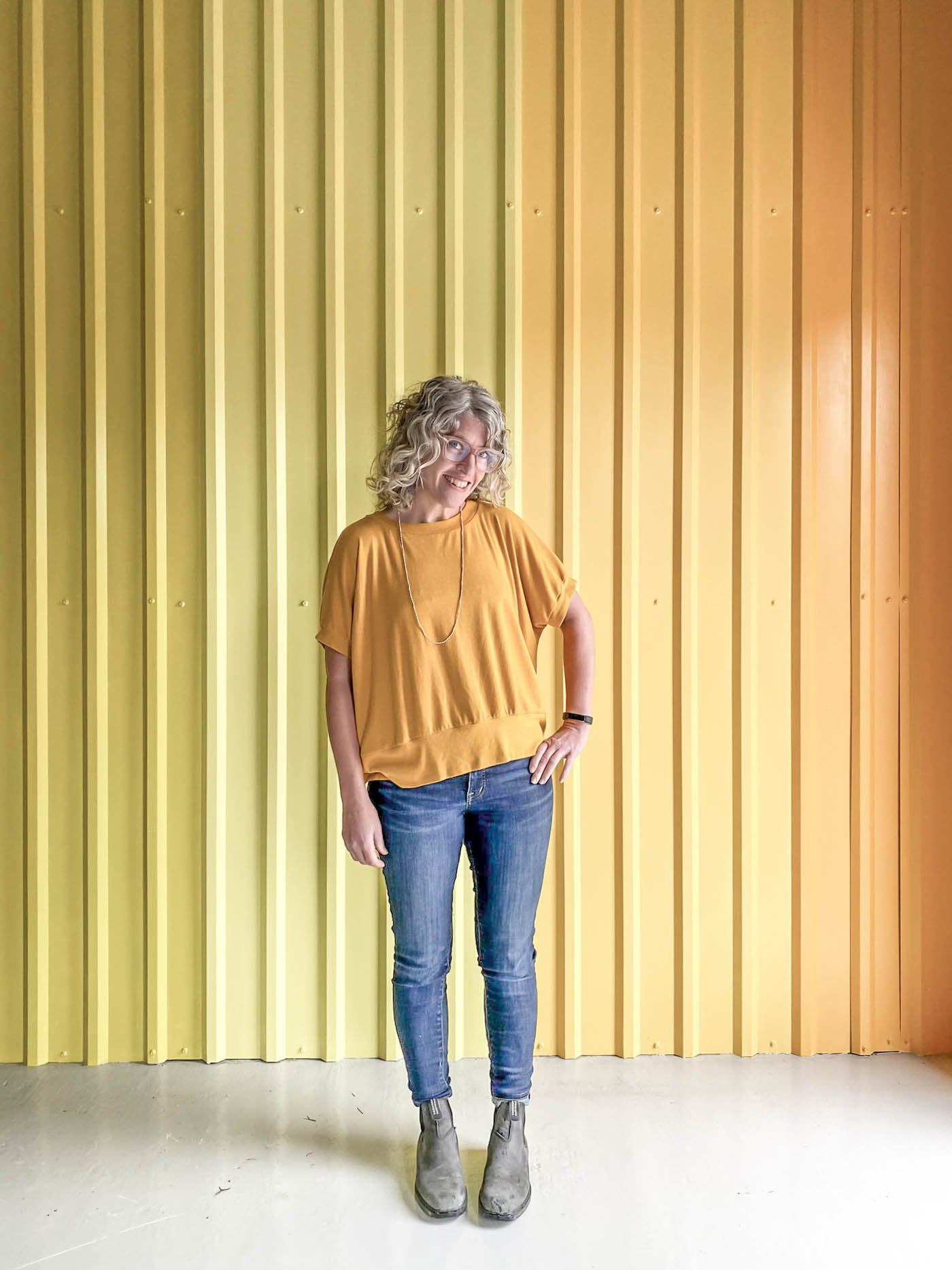 Jaime wearing a golden yellow Hosta tee, jeans and black boots, standing in front of a corrugated yellow ombre wall.