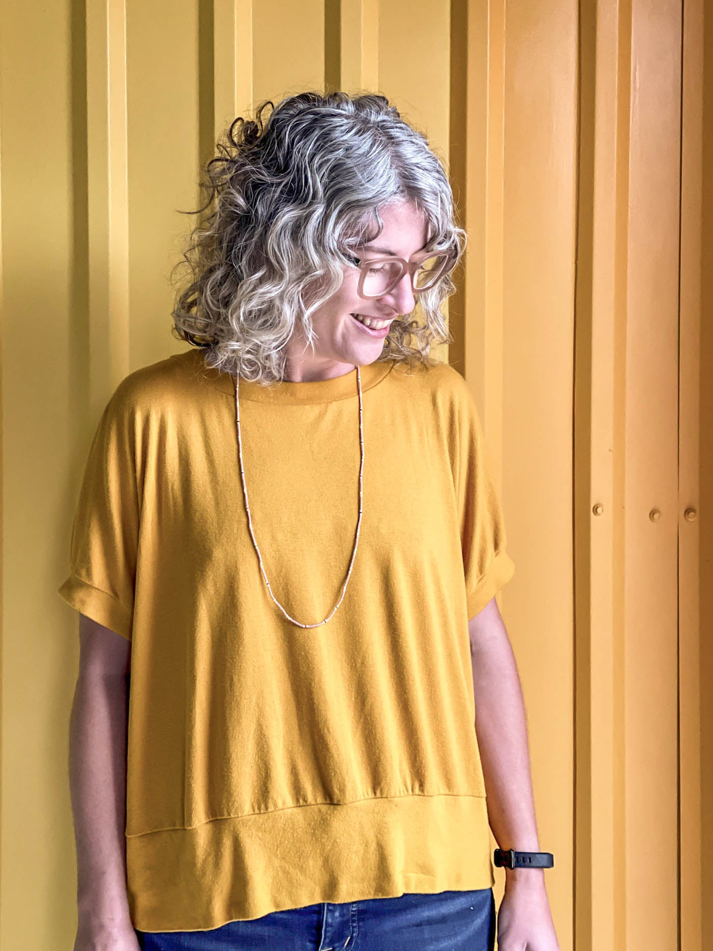 Close up of Jaime looking down, wearing a golden yellow Hosta tee, standing in front of a corrugated yellow ombre wall.