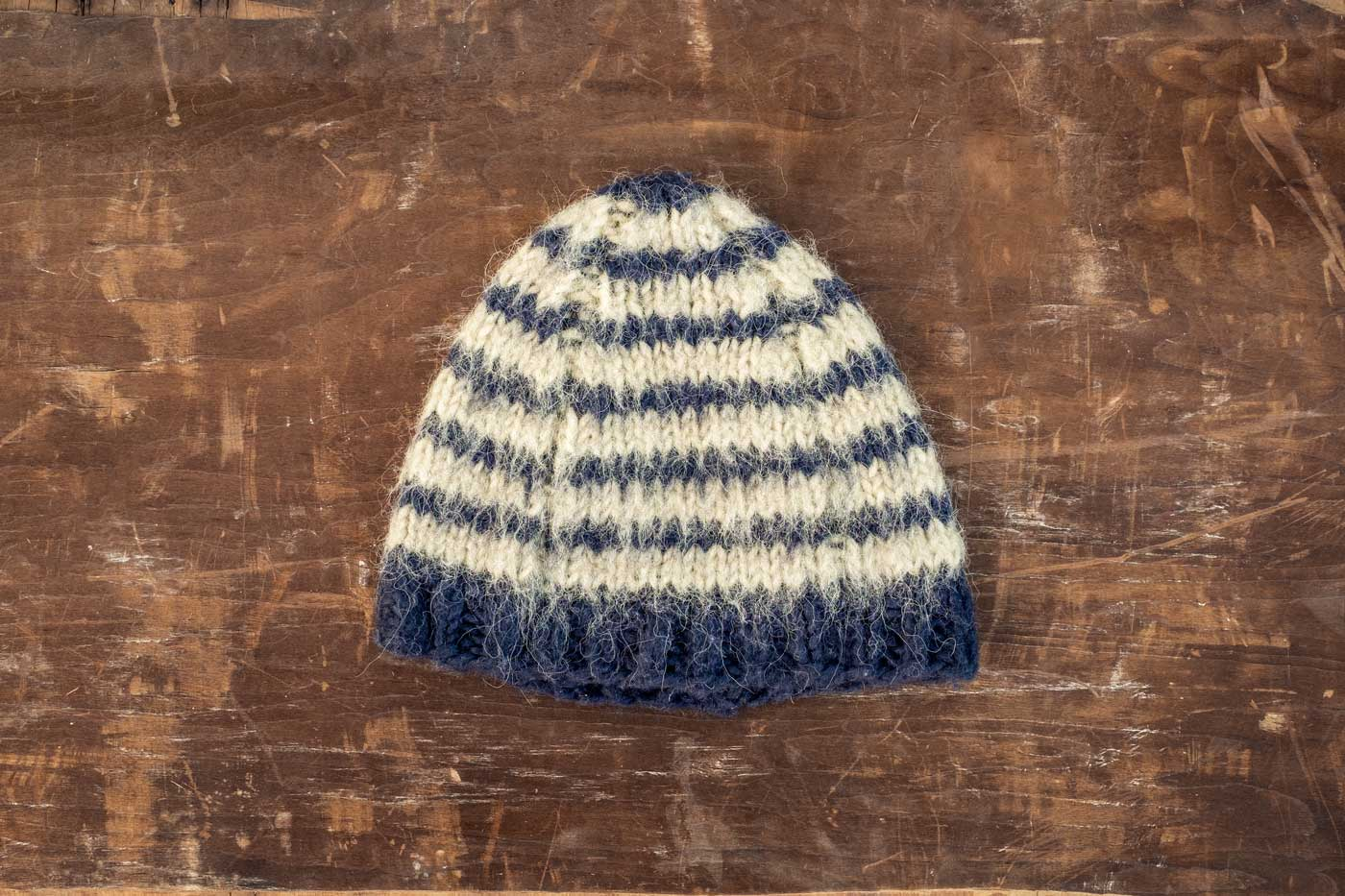 Blue and white brushed wool hat laying flat on dark wood.