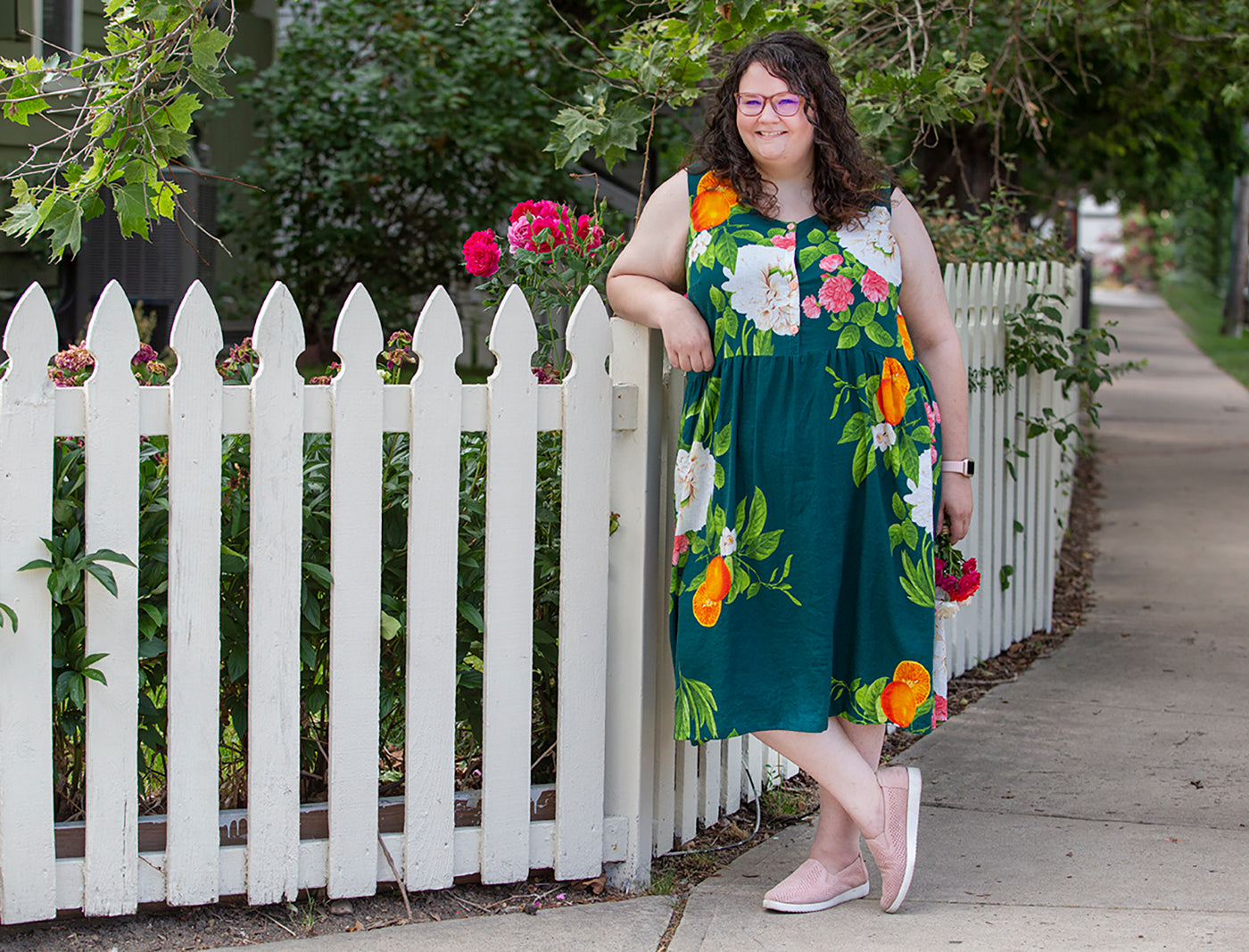 This is an image of a woman wearing a colorful. flower covered dress standing next to a white picket fence and rose bush