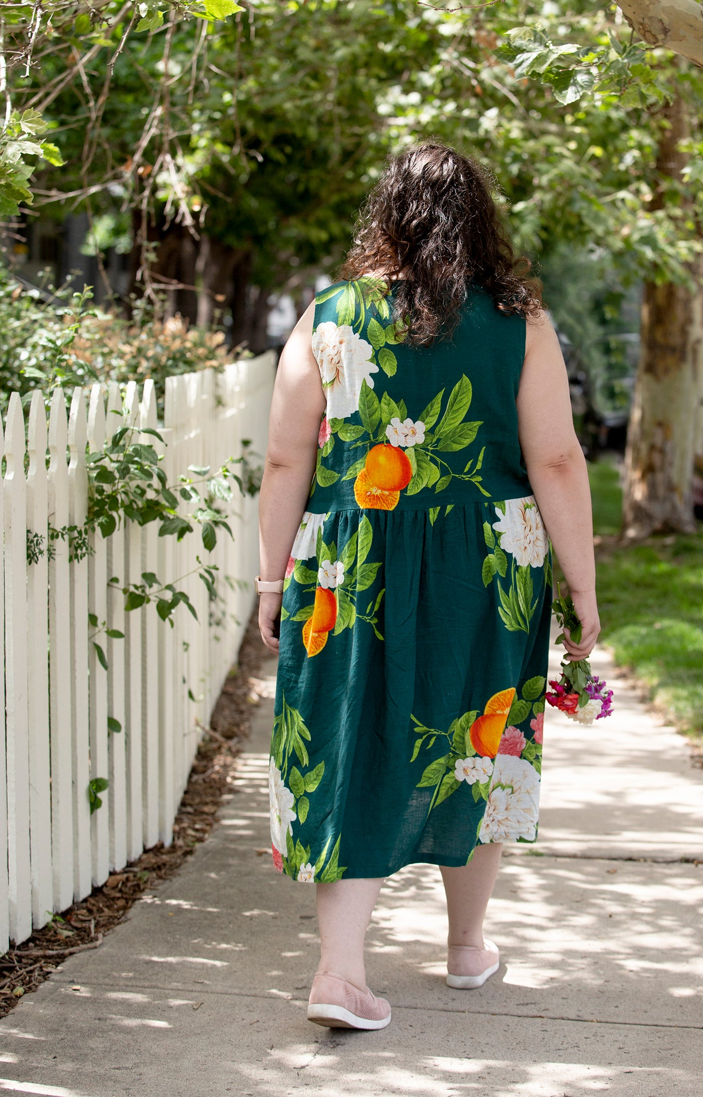 This is an image of a woman wearing a flower covered dress walking away down a side walk next to flowers and a white picket fence.