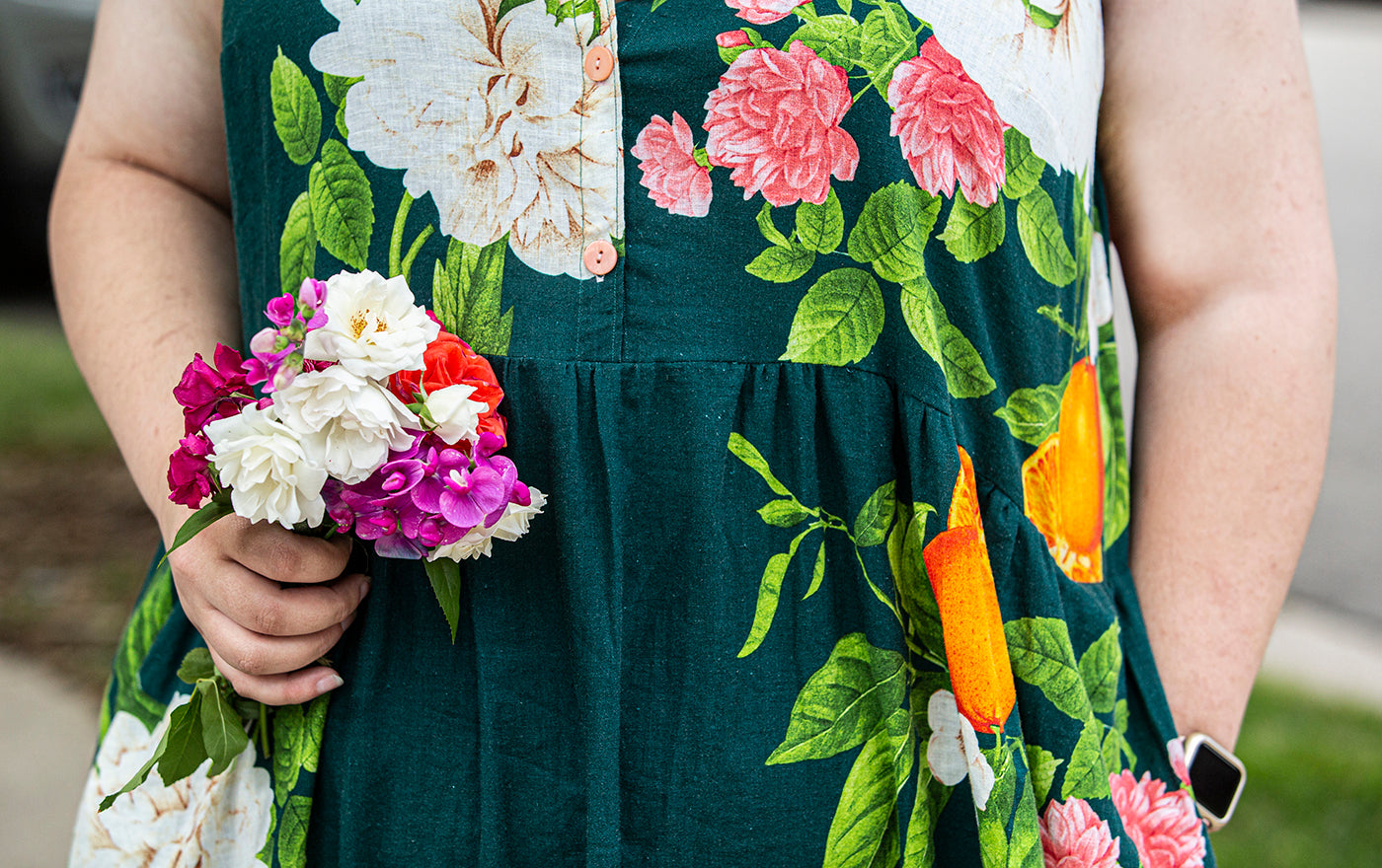 This is an up close image of the pleated waste of a dress covered in flowers. The woman wearing the dress has one hand in a pocket and is holding a bouquet of flowers in the other hand