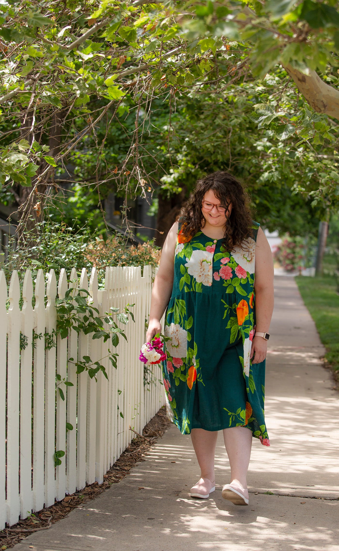 This is an image of a woman wearing a flower covered dress standing next to flowers and a white picket fence.
