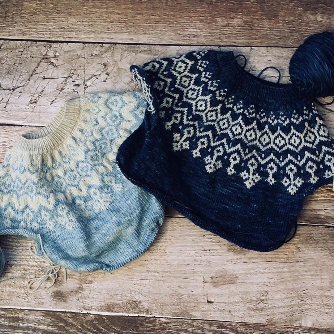 Layflat photograph of two sweaters showing knitting in progress.  Left one is a light blue and white.  Right sweater is a dark navy and white.  Background is a rustic wood floor.
