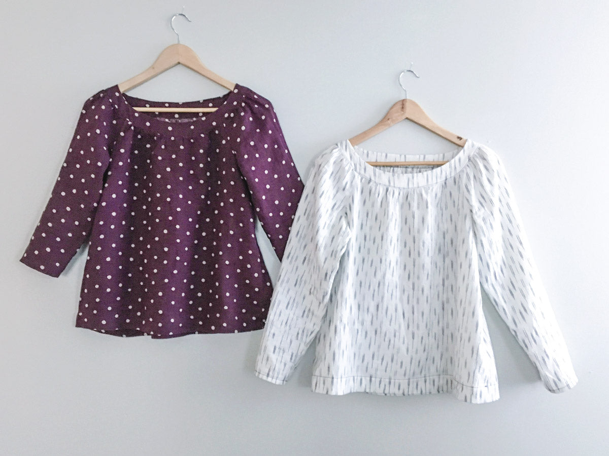 Two shirts, a 3/4 length sleeve and a long sleeved Sailor Top hanging on a white wall