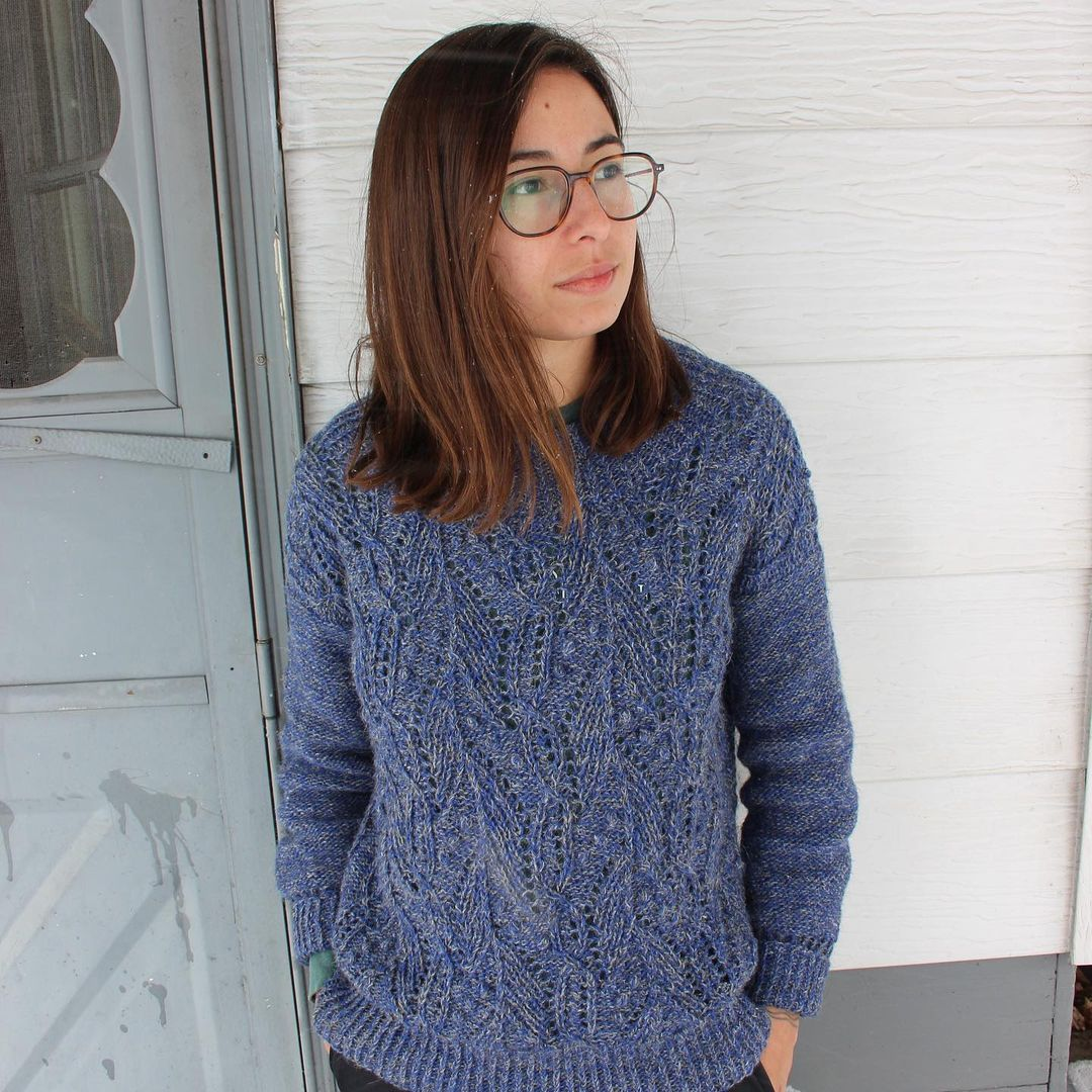 Luna stands outside near a porch door, wearing the denimy blue Atlantica pullover she recently knit.