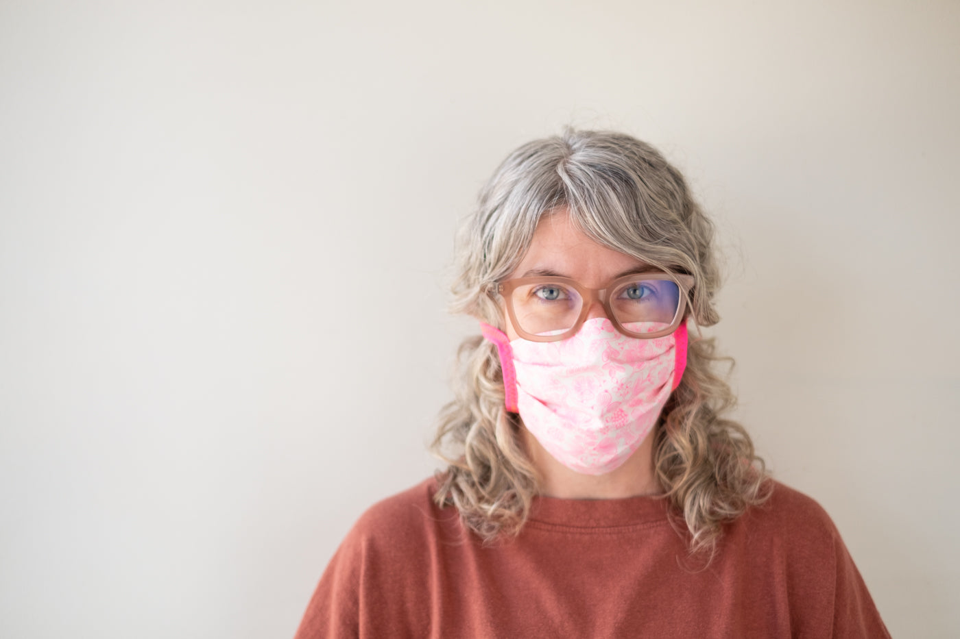 Jaime wearing a pink face mask with bright pink ties standing in front of a white wall.