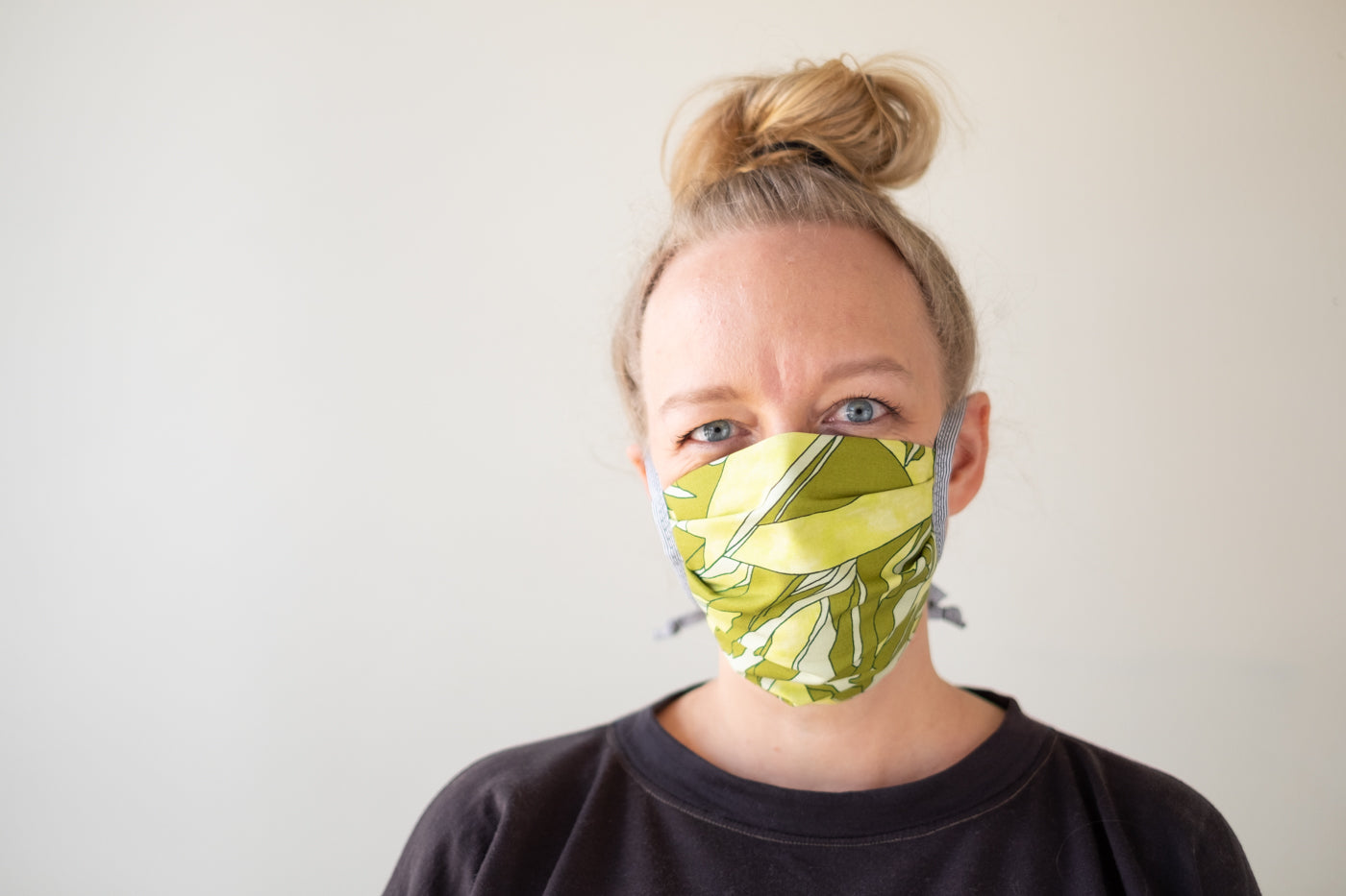 A closely cropped photo of Amber against a white background, she is wearing a fabric mask in an abstract green print and her hair is in a top-knot.