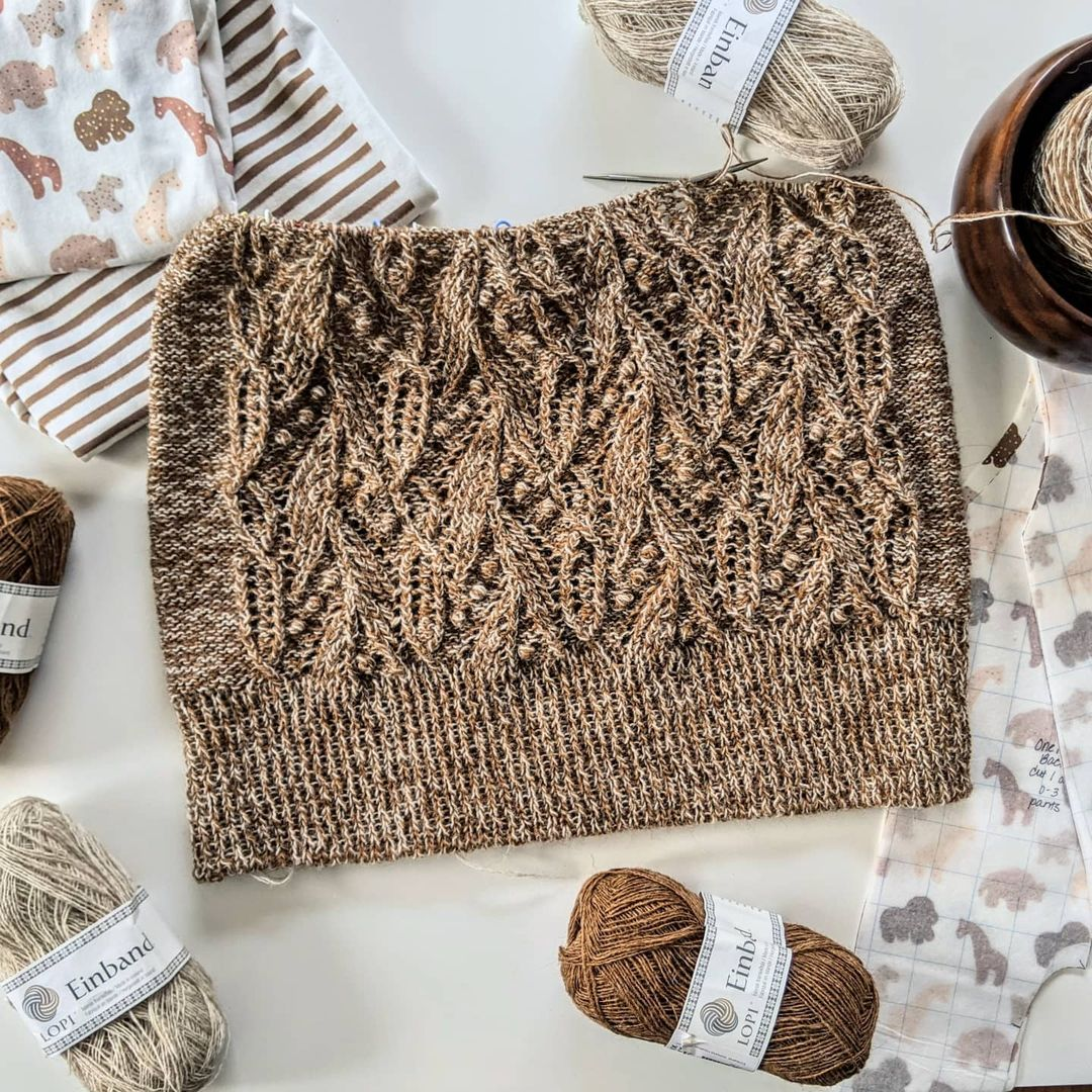 An in-progress Atlantica sweater in warm almond hues lays flat on a white surface. It is surrounded by it's yarn balls, and a cute sewing project in similar colors that is also in-progress, using adorable fabric featuring an animal cookie print.