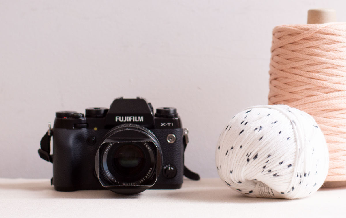 A spool of macrame cord, a ball of yarn and a camera on a white background.