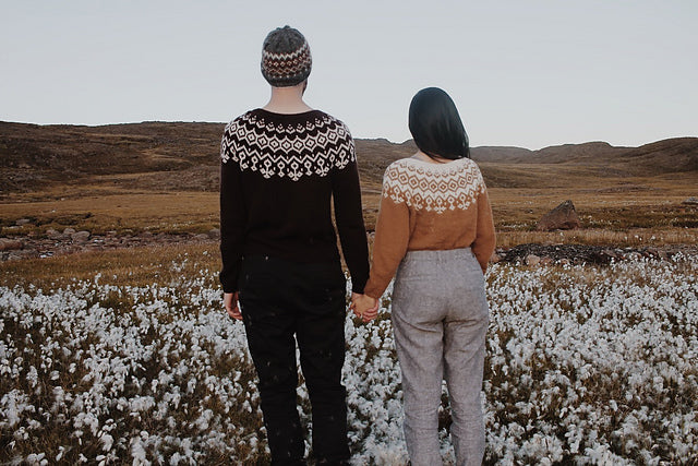 Photo Credit to Ravelry boy and girl standing in a field with their backs facing camera.  Couple is holding hand showing their knitted sweaters.  The man is wearing a knitted hat with a black and white sweater and black pants.  The women has her dark brown hair to the side showing the back of her mustard yellow and white knitted sweater wearing medium grey tweed pants.