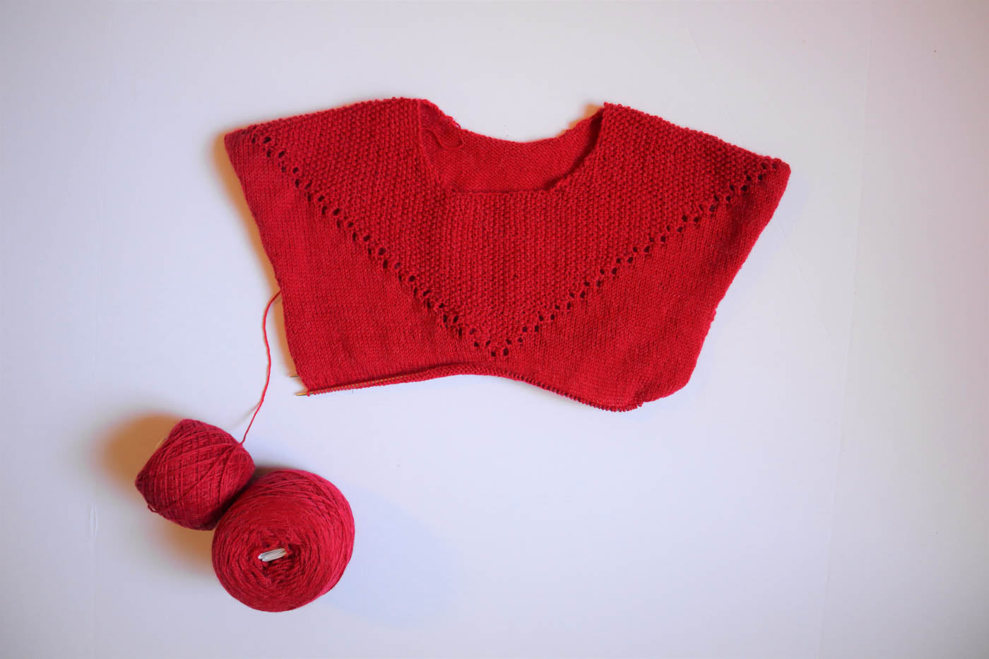 A red sweater being knitted