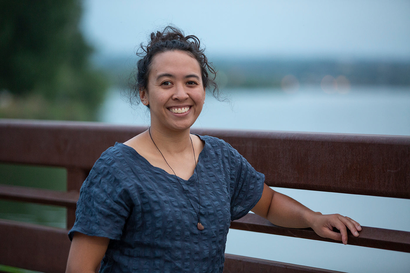 This is an image of a woman wearing a blue linen shirt standing outside on a bridge