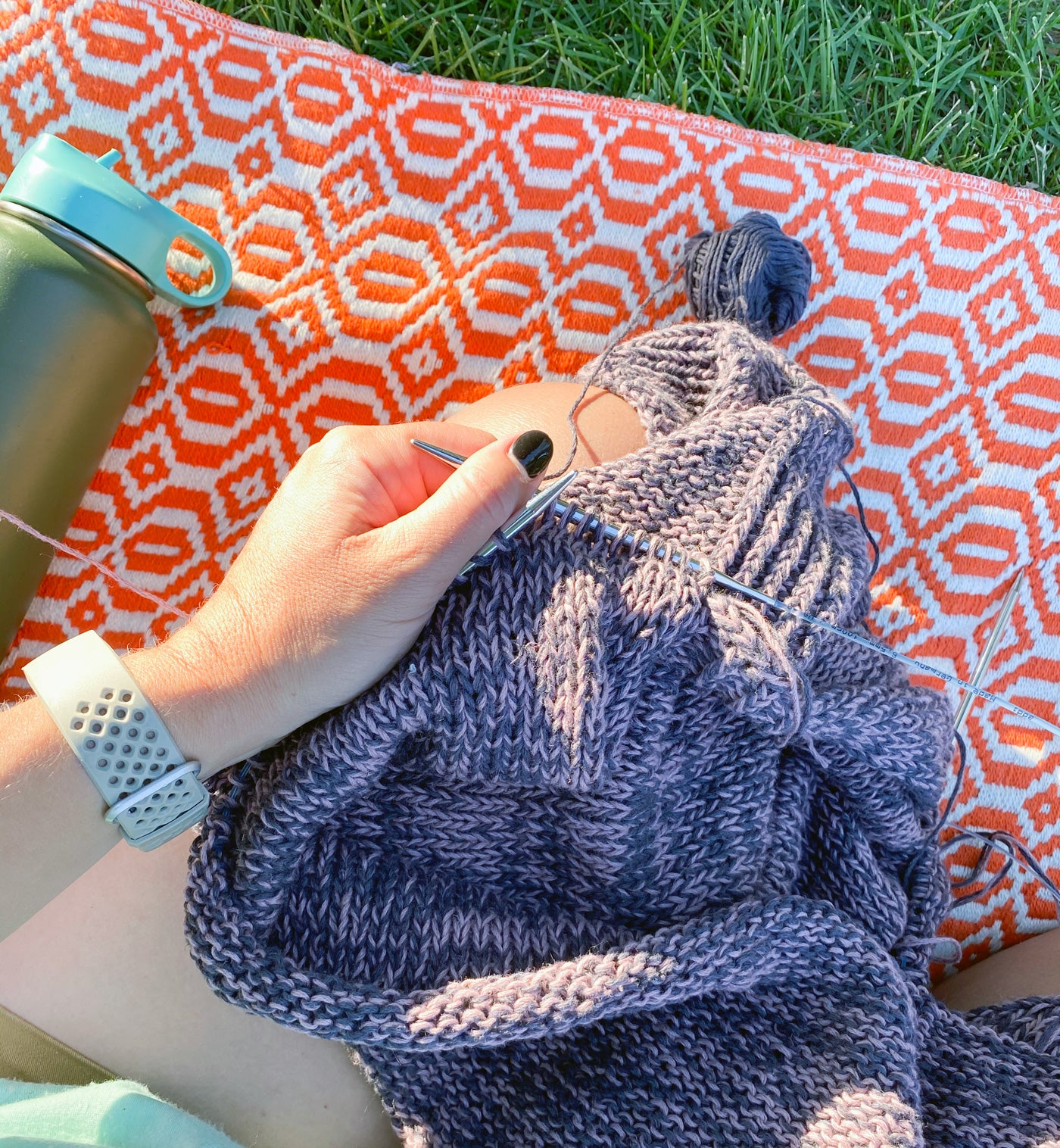 A close-up of someone's hands knitting a cotton garment, they sit crosslegged on a poppy-red and white patterned picnic blanket on lush green grass, with a green metal water bottle laying next to them.