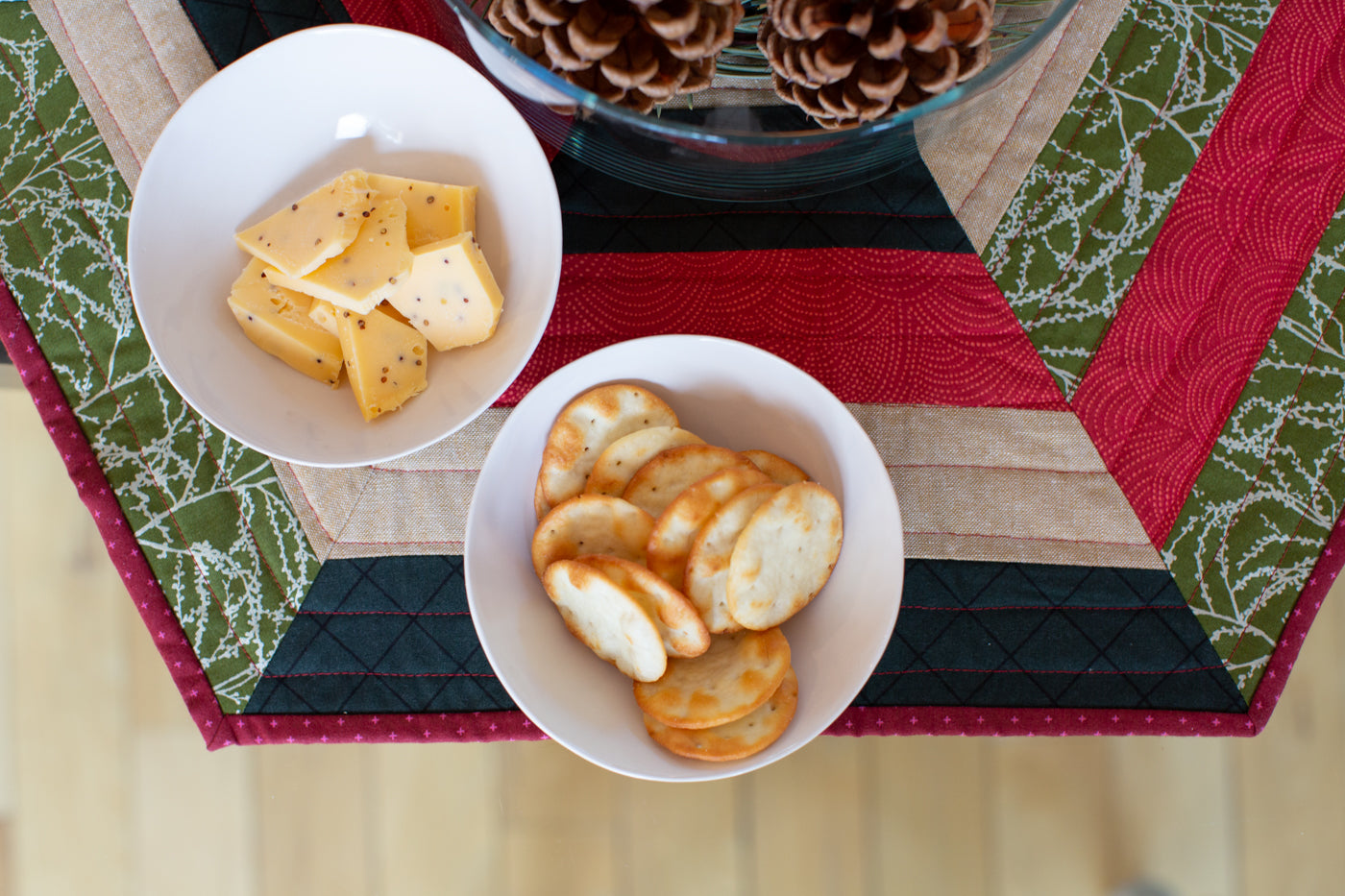 Photograph of looking at half of the hexagon centerpiece in Christmas green, red, a tan and black.  Two white small bowls are on the centerpiece one filled with sliced of mustard cheese and the other with white round crackers.