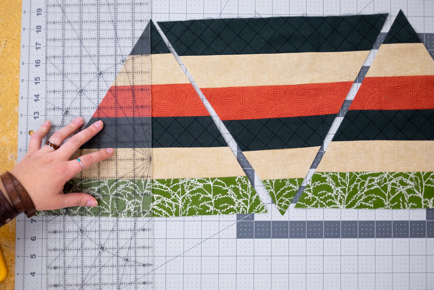 Material triangles laid out with a clear ruler over top showing them being lined up.  Triangles colors cut in lines of green with metallic sliver, soft yellow, black and red, sewn together to make a triangle.