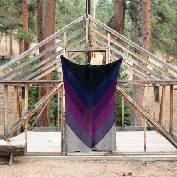 A large knit blanket in a chevron ombre of purples. It is held up in front of the frame of a cabin in the woods, and is wider and almost as tall as the doorway.