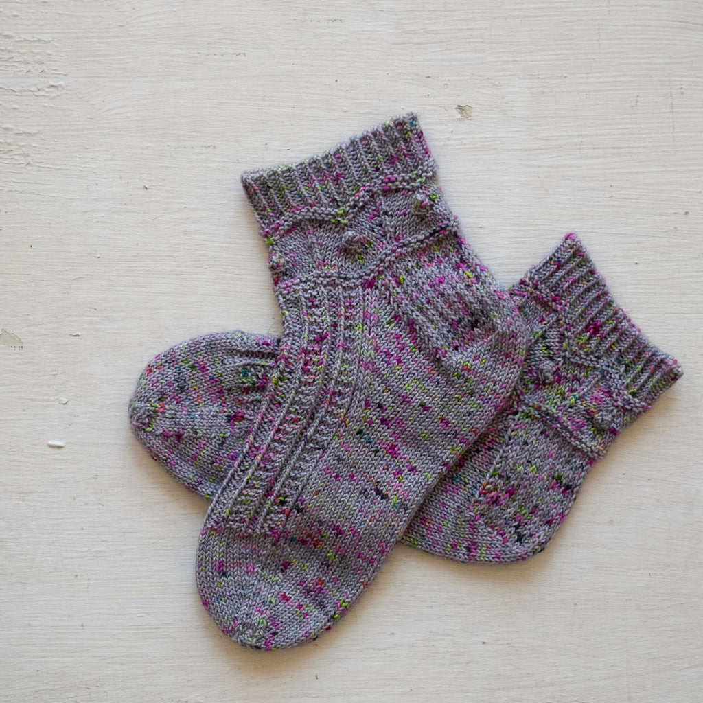 Handknit socks with loads of texture: bobbles, chevrons, and garter ridges, worked up n a grey yarn lightly speckled with magenta, green and blue.