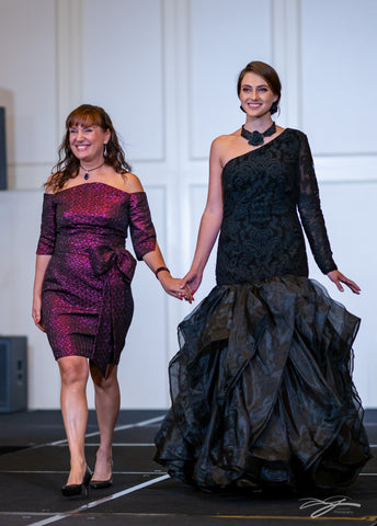 Chicago Fashion Designer Artist Couturier Alesia Chaika in her custom purple triangle jacquard gown with bean neckline presenting Black Rose mermaid evening lace organza dramatic skirt gown at Model icon Fashion Week Palmer House Hilton Hotel Chicago