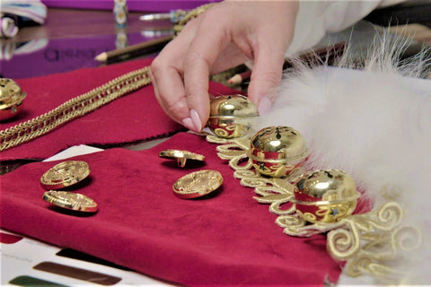 Crafting the traditional Santa Claus costume with gold jingle bells, white fur, red velvet at Alesia Chaika atelier located in Buffalo Grove, Illinois USA