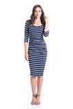 The Midi Body Con dress in navy and ivory stripes is a form-fitting dress that hits just below the knee. This dress features a feminine scoop neckline, ruching to hide side bumps, and three-quarter sleeves.