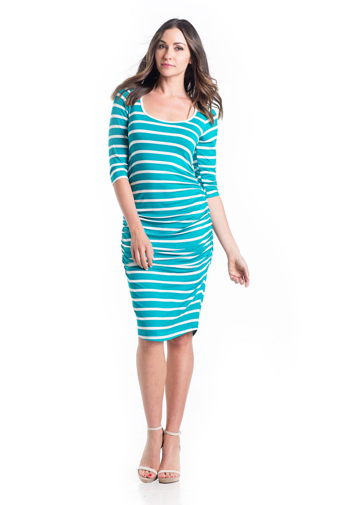 The Midi Body Con dress in teal and ivory stripes is a form-fitting dress that hits just below the knee. This dress features a feminine scoop neckline, ruching to hide side bumps, and three-quarter sleeves.