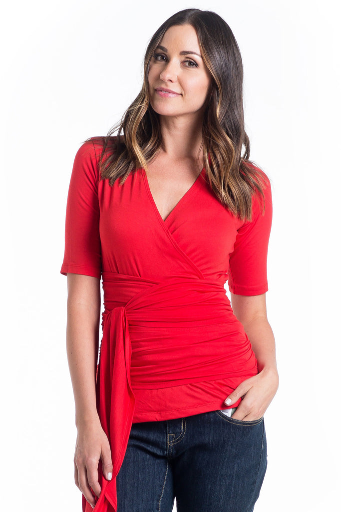 The Bella Top in Tomato is a wrap top with an adjustable neckline, it shows just enough to keep it sexy without showing too much and is great for nursing. The wrap accentuates or hides your midsection as you please.  It is a great top for women and maternity.
