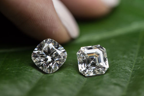 Single diamond in a pair of tweezers with diamonds on a tray in the background