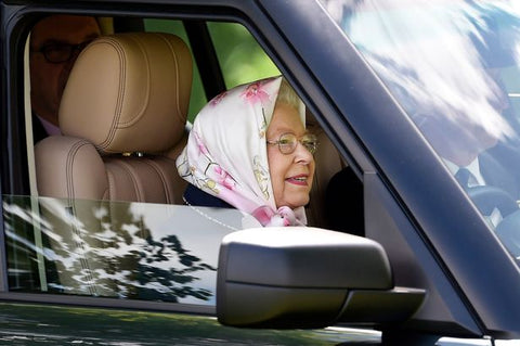Queen driving a car with a headscarf on