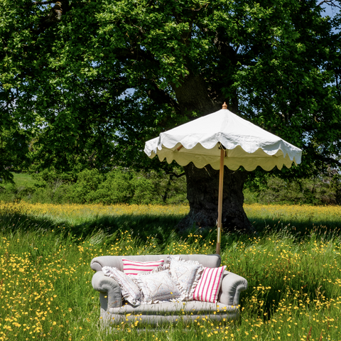 Holly Octagonal Parasol in a field with a couch