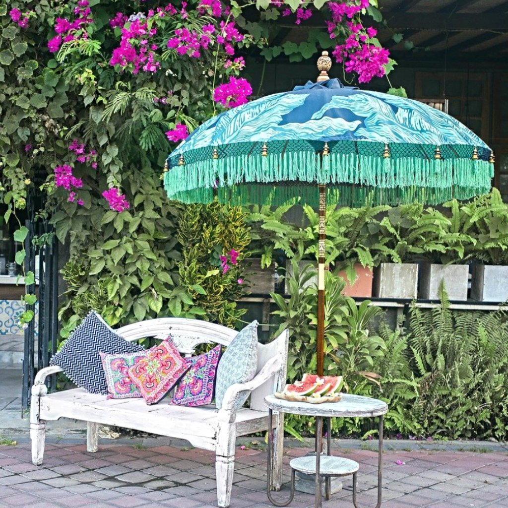Nina parasol. Digital printed waterproof canvas dark blue palm leaf banana leaf design blue and green. East London parasol company garden umbrella made in bali. Lifestyle shot