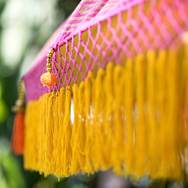 Whitney- East London Parasol Company pink Bali garden umbrella with yellow and orange tassels, pom poms and fringing. Stunning, colourful parasol for an elegant summer garden.