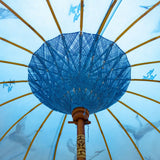 East London Parasol Company Bali Bamboo 2m garden umbrella. Flying birds cranes with white, blue and indigo. Handmade and handpainted with fringing and tassels in shades of white