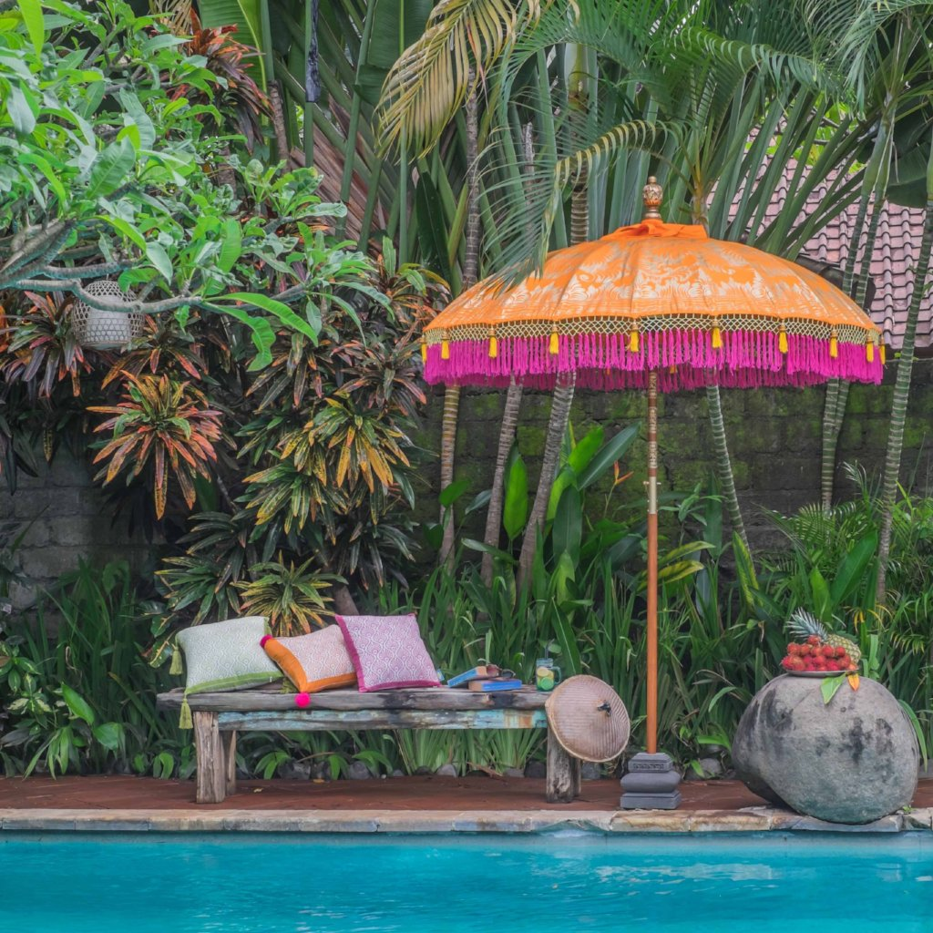 Etta. Vibrant orange Bali garden parasol, artisan painted with gold and with handmade pink fringing. The most beautiful garden umbrella and summer accessory. Perfect for patios, pools, picnics and weddings. The ultimate stylish garden decoration, luxurious, colourful and handmade.