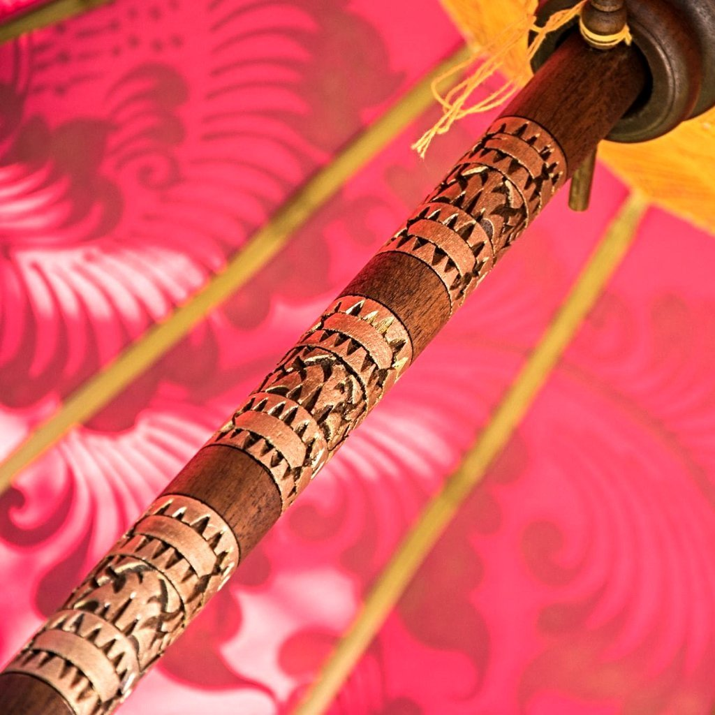 East London parasol company Etta garden parasol or umbrella. Handmade in Bali, orange and gold painted with pink tassels. Wooden framed with carving.