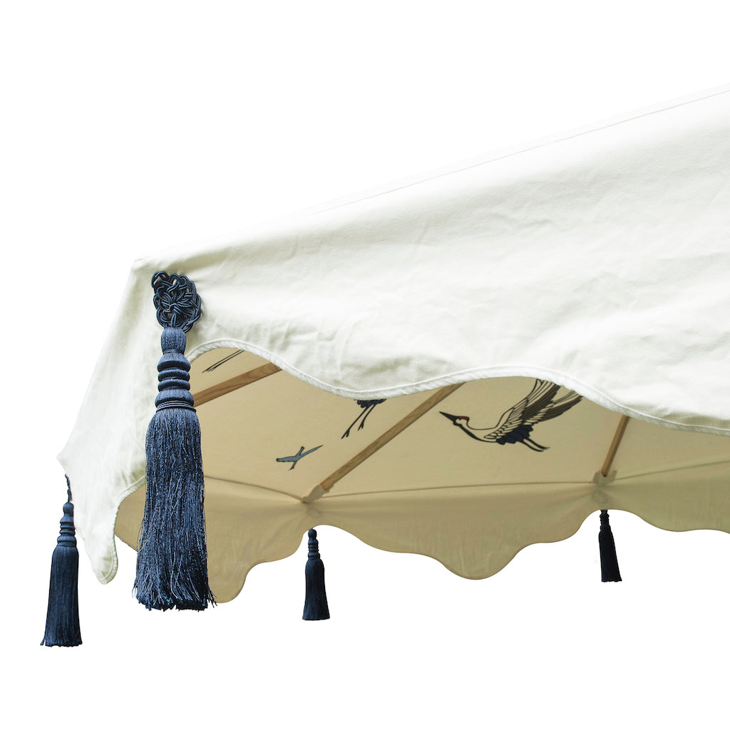 Big Lexi, 3m width waterproof canvas Garden parasol in natural cotton  with flying birds in grey, red and indigo blue on the inside. Screen printed garden umbrella with stunning indigo tassels. Elegant, chic and calming, the ultimate luxury garden decoration. The canopy is easily removable. The perfect umbrella for gardens, summer, patios, pool side and terraces. A fabulous garden accessory for a party.