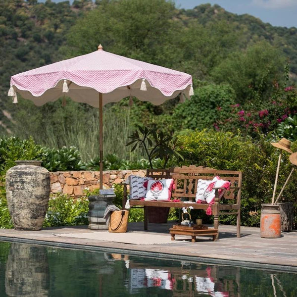 East London Parasol Company. Big Pink Aretha, Indian inspired garden parasol. Printed cream and pink chevron colourful garden umbrella. 3m wooden waterproof cotton canvas with rose pink zig zags and white. The edges are an arabian-influenced shape with handmade natural cotton tassels.  Perfect show stopping garden umbrella for an elegant garden or pool, or beside a sun lounger, for an event or wedding. Luxurious, flamboyant and colourful garden accessories.