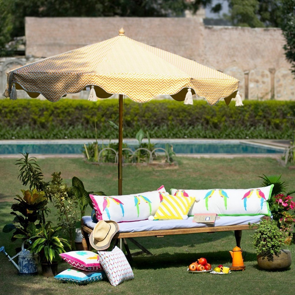 East London Parasol Company. Big Orange Aretha, stunning 3m wooden frame garden parasol. Natural waterproof cotton canvas with printed orange zig zags and yellow interior, with natural cotton tassels. The edges are an arabian-influenced shape. The canopy is removable. The ultimate garden decoration. Perfect show stopping garden umbrella for an elegant dining area or pool, or beside a sun lounger, for an event or wedding. Luxurious, flamboyant and colourful garden accessories.
