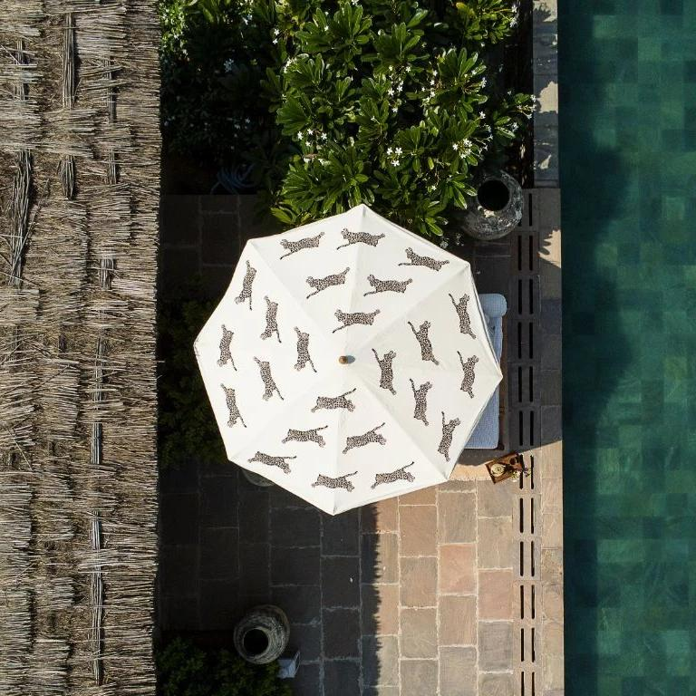 In stock 3m width Waterproof canvas Big Gloria garden umbrella. Leopard printed garden parasol with neutral beige and creams. A show stopping garden umbrella with wooden frame and tassels. The perfect umbrella for gardens, summer, patios, pool side and terraces. On the leopard print, maximalism animal safari trend.