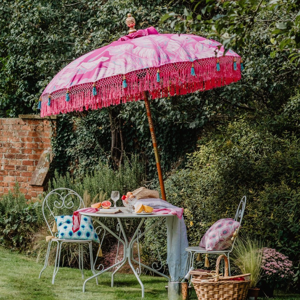 Pink Nina- waterproof canvas with pink and blue leaf design garden umbrella. Balinese garden parasol perfect for a picnic, patio, through your table with an umbrella hole or by your sun lounger at the pool. Very beautiful, colourful summer garden decorations. Make your outdoor space chic, elegant and glamorous with this colourful tasseled bali parasol..