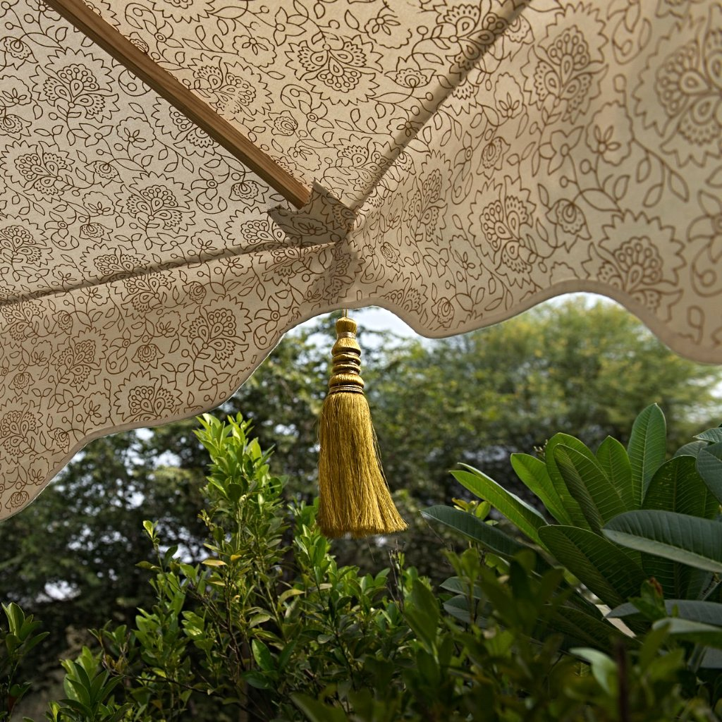 Big Liberace, stunning 3m wooden frame cream and gold garden parasol. Natural cotton canvas with gold block print inside and luxurious gold tassels. The edges are an arabian-influenced shape with handmade adornments. The canopy is removable. The ultimate garden decoration. Perfect show stopping garden umbrella for an elegant dining area or pool, or beside a sun lounger, for an event or wedding.