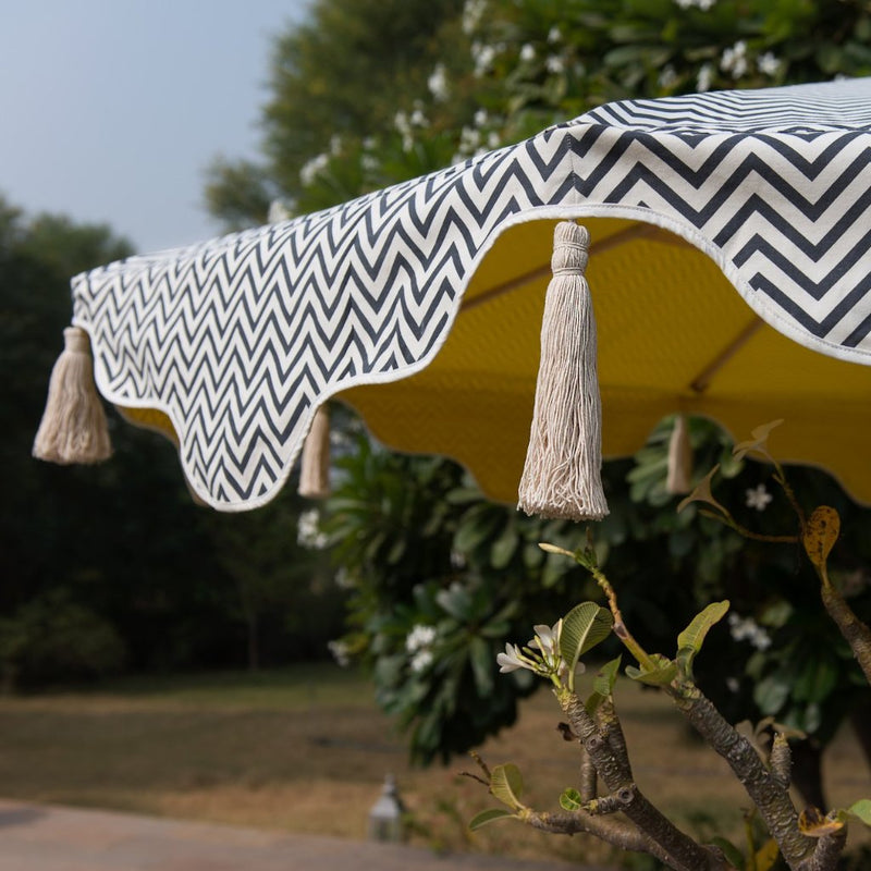 3m Zigzag and yellow garden parasol. Block printed natural coloured waterproof cotton canvas with charcoal zig zags and primrose yellow and a wooden garden umbrella frame of 3m. The edges are an arabian-influenced shape with handmade natural cotton tassles.  Perfect  show stopping garden umbrella for an elegant garden or pool. The most fabulous garden decoration.