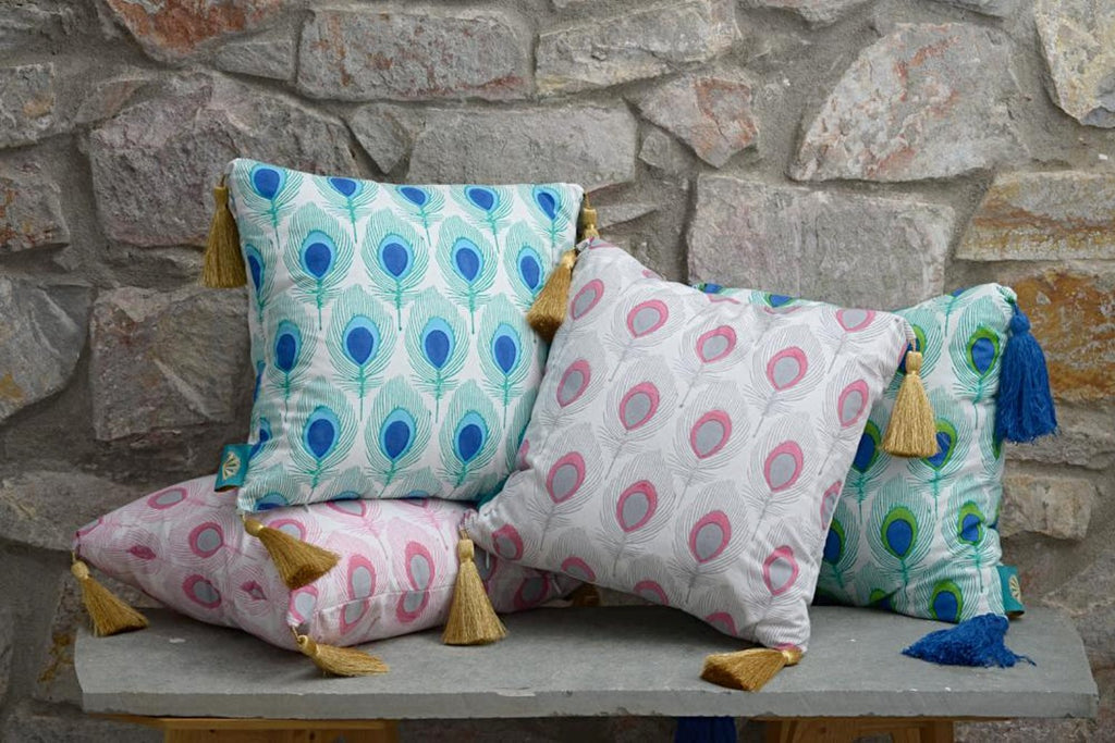 Pink grey turquoise and green peacock tassel cushions from East London Parasol company. With gold tassles block printed in India